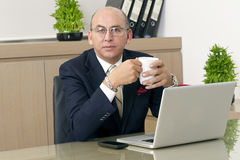 Mature Man in formalwear drinking coffee while sitting at his working place Royalty Free Stock Images