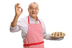 Mature man with a freshly baked pie making an ok sign. Isolated on white background royalty free stock image