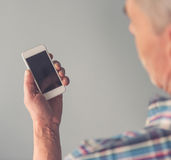 Mature man with gadget. Cropped image of mature man using a smartphone, on gray background royalty free stock photos