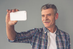 Mature man with gadget. Handsome mature man in casual wear is doing selfie using a smart phone and smiling, on gray background royalty free stock images