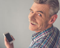 Mature man with gadget. Handsome mature man is using a smart phone, looking at camera and smiling, on gray background stock photo