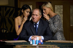 Mature man with gambling chips at poker table, flanked by young women whispering, portrait Royalty Free Stock Photos