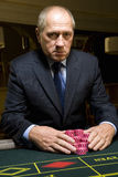 Mature man with gambling chips at roulette table, portrait Stock Images