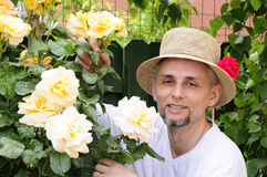 Mature man in garden between roses Royalty Free Stock Photos