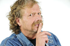 Mature man gesturing for quiet. Portrait of mature man with finger on lips gesturing for quiet or silence, isolated on white background Stock Images