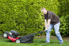 Mature man getting ready to do yard work. Horizontal photo of a mature man, dressed in blue jeans and t-shirt, while getting ready to use an old gas lawnmower Royalty Free Stock Photography