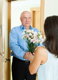 Mature man giving bunch of flowers to  woman Stock Photo