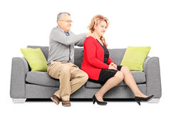Mature man giving a massage to his wife on couch. Mature men giving a back rub to his wife seated on couch isolated on white background Royalty Free Stock Image