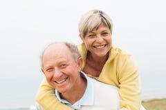 Mature man giving woman piggyback Stock Image