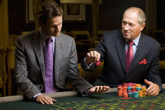 Mature man with giving young man gambling chip at roulette table Stock Image