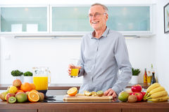 Mature man with a glass of orange Juice in the kitchen Royalty Free Stock Image