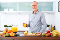 Mature man with a glass of orange Juice in the kitchen, smiling Stock Photos