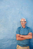 Mature man with glasses against a blue wall Stock Photos