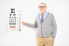 Mature man with glasses pointing towards eyesight test Stock Images