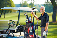 Mature man with a golfcart on the green royalty free stock images