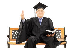 Mature man in graduation gown on bench giving a thumb up. Mature man in graduation gown seated on wooden bench holding a book and giving thumb up isolated on Stock Image