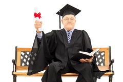 Mature man in graduation gown on bench holding a diploma and boo Royalty Free Stock Photo