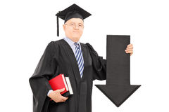 Mature man in graduation gown holding big black arrow pointing d Stock Photos
