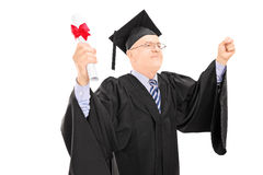 Mature man in graduation gown holding diploma and gesturing succ Royalty Free Stock Photography