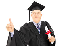 Mature man in graduation gown holding a diploma and giving thumb. Up isolated on white background Stock Photography
