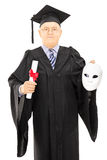Mature man in graduation gown holding diploma and theater mask Royalty Free Stock Image