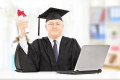 Mature man in graduation gown posing with diploma and laptop Royalty Free Stock Photography