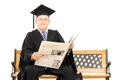Mature man in graduation gown reading newspaper seated on bench Royalty Free Stock Images