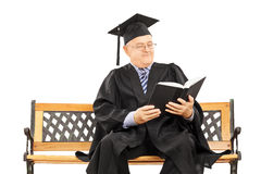 Mature man in graduation gown seated on bench reading book Stock Photos