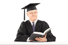 Mature man with graduation hat reading book seated on table. Mature man with graduation hat reading a book seated on table isolated on white background stock images