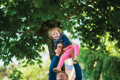 Mature man with grandchild. Cute laughing girl. Mature men tossing up a child. Happy granddaughter laughing. Fun play family lifestyle Stock Photography
