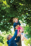 Mature man with grandchild. Cute laughing girl. Mature men tossing up a child. Happy granddaughter laughing. Fun play family lifestyle concept Royalty Free Stock Image