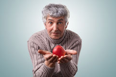 A mature man with gray hair and green eyes wearing casual sweater holding red delicious apple in his hands having surprised expres Stock Photography