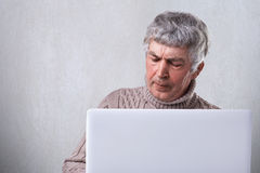 A mature man with gray hair siting in front of his laptop having dissatisfied expression and wrinkles on his face isolated over wh Stock Photo