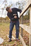 Mature Man Hammering Nail Into Repaired Fence Royalty Free Stock Image