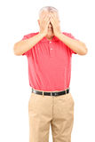Mature man with hands over his eyes Stock Images