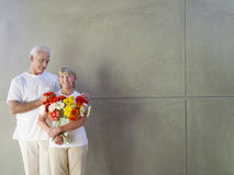 Mature man with hands on woman's shoulders, woman with vase of flowers, smiling, portrait Royalty Free Stock Image