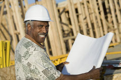 Mature Man In Hardhat With Blueprint At House Construction Site. Portrait of a smiling mature man in hardhat holding blueprint in front of house construction Stock Photography