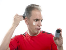 The mature man has reflected on application of a man's cream against wrinkles Stock Photo