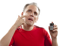 Mature man has reflected on application of a man's cream against wrinkles Royalty Free Stock Image