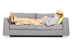 Mature man with hat over his head sleeping on a sofa. Isolated on white background Royalty Free Stock Image
