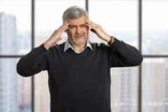Mature man have strong headache. stock photos