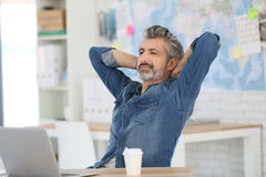 Mature man having a break in front of laptop Royalty Free Stock Photo