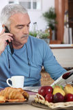 Mature man having breakfast. And reading newspaper royalty free stock photo