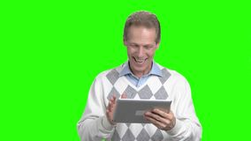 Mature man having communication via internet. Middle-aged man making a video call by his pc tablet to communicate with children, green screen stock video