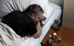 Mature man having difficulty falling asleep at night thus awake. Mature man staring at alarm clock while trying to fall asleep. Insomnia concept Royalty Free Stock Photo