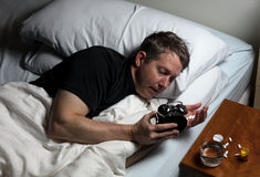 Mature man having difficulty falling asleep at night thus taking. Mature man checking time on alarm clock while preparing to take medicine. Insomnia concept Royalty Free Stock Photo