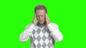 Mature man having headache, green background. Middle-aged man suffering from headache on chroma key background stock footage