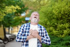 Mature man having heart attack. Outdoors stock images