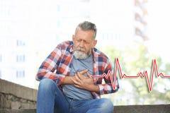Mature man having heart attack stock image