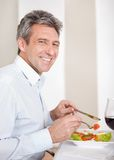Mature man having lunch at home Stock Photography